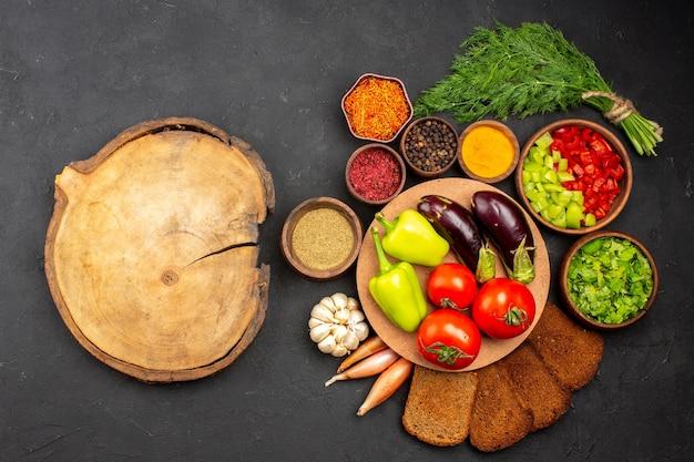 Widok z góry świeże dojrzałe warzywa z zieleniną i ciemnymi bochenkami chleba na ciemnej powierzchni sałatka jedzenie posiłek zdrowie warzywa