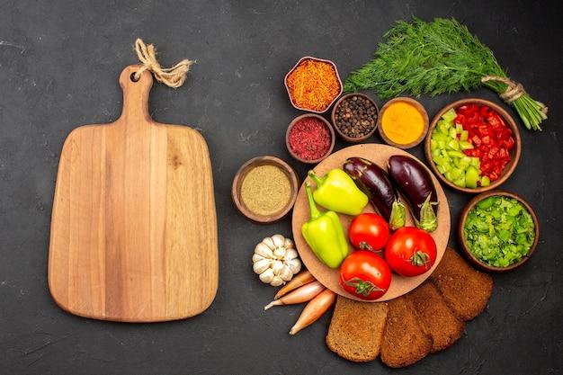 Widok z góry świeże dojrzałe warzywa z zieleniną i ciemnymi bochenkami chleba na ciemnej powierzchni sałatka jedzenie posiłek zdrowie warzywo