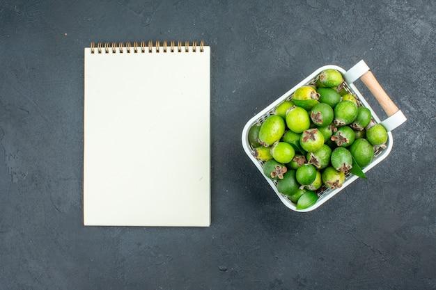 Widok z góry świeże feijoas na notebook z plastikowym koszem na ciemnej powierzchni