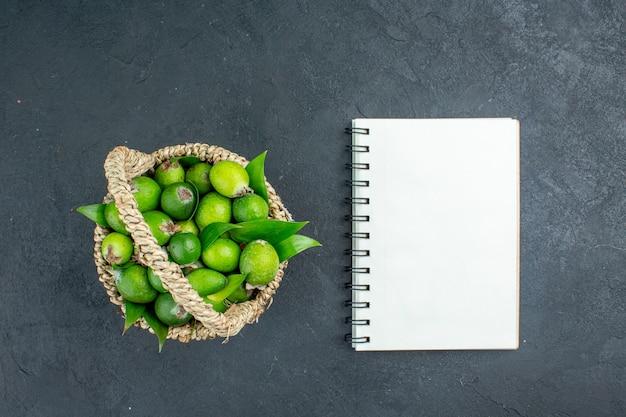 Widok z góry świeże feijoas w koszyku notebook na ciemnej powierzchni