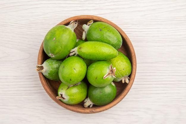 Widok z góry świeże feijoas wewnątrz talerza na białym tle kolor owoców tropikalnych egzotycznych dojrzałych diet