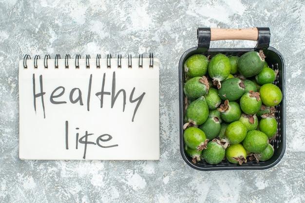 Widok z góry świeże feykhoas w koszyku zdrowego życia napisane na notatniku na szarej powierzchni