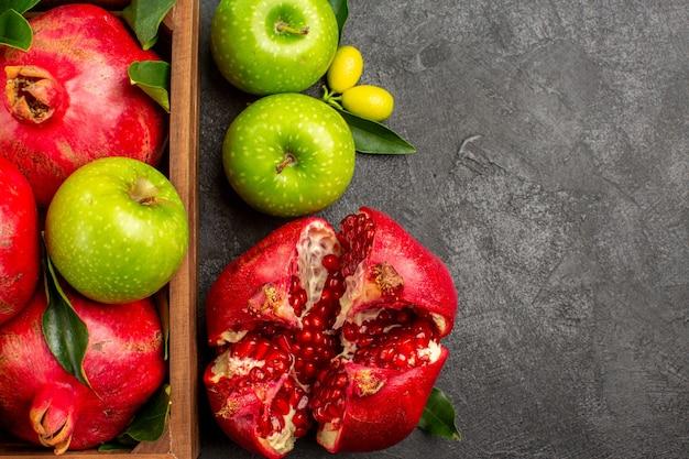 Widok z góry świeże granaty z zielonymi jabłkami na ciemnej powierzchni kolor dojrzałych owoców