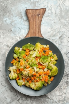 Widok z góry świeże i zdrowe sałatki warzywne na drewnianą deską do krojenia na białym tle