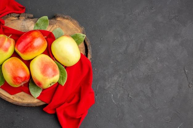 Widok z góry świeże jabłka dojrzałe owoce na czerwonej tkance i szarym stole dojrzałe świeże owoce