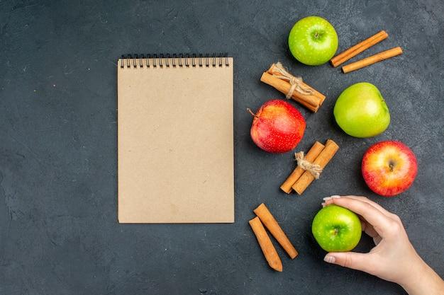 Widok z góry świeże jabłka laski cynamonu notebook jabłko w kobiecej dłoni na ciemnej powierzchni