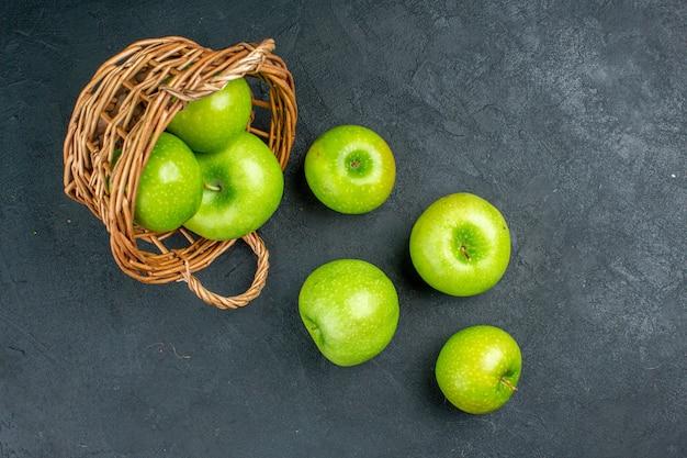 Widok z góry świeże jabłka rozrzucone z wiklinowego kosza na ciemnej wolnej powierzchni