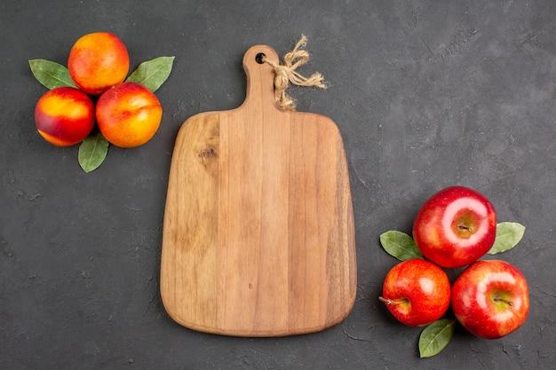 Widok z góry świeże jabłka z brzoskwiniami na ciemnym stole w kolorze świeżych dojrzałych owoców