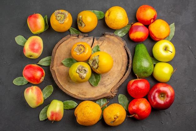 Widok z góry świeże jabłka z gruszkami i persimmons na ciemnym drzewie stołowym łagodnie świeże dojrzałe