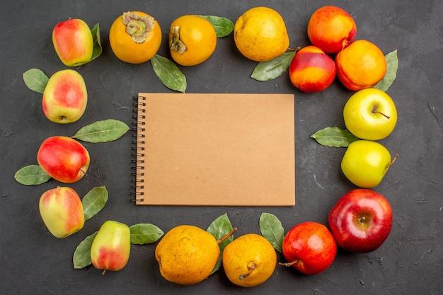 Widok z góry świeże jabłka z gruszkami i persimmons na ciemnym stole, aksamitne świeże dojrzałe