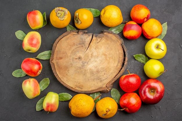Widok z góry świeże jabłka z gruszkami i persimmons na ciemnym stole łagodnym dojrzałym świeżym drzewem