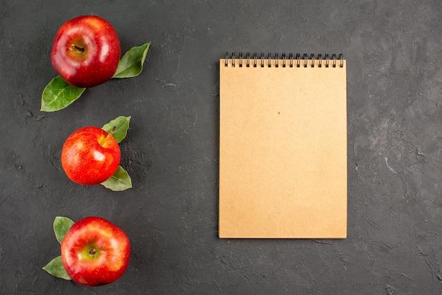 Widok z góry świeże jabłka z notatnikiem na ciemnym stole dojrzałe owoce czerwone świeże