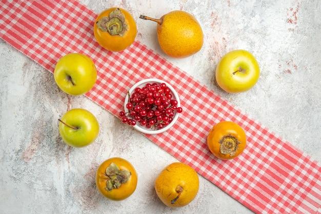 Widok z góry świeże jabłka z persimmons na białym stole zdrowie drzewa owocowego jagody