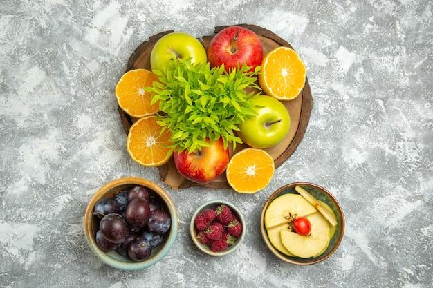 Widok z góry świeże jabłka z pokrojonymi pomarańczami i śliwkami na białym tle dojrzałe, łagodne owoce świeże jabłko