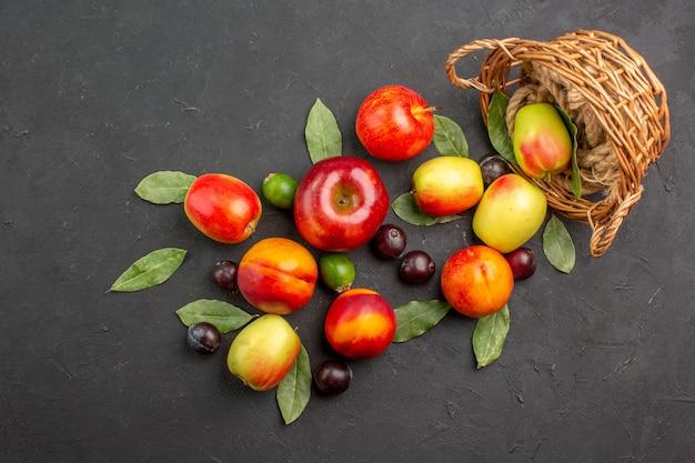 Widok z góry świeże jabłka ze śliwkami i brzoskwiniami na ciemnym stole dojrzały sok łagodny