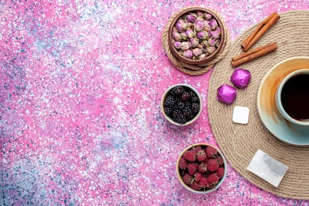 Widok z góry świeże jagody maliny i jeżyny z filiżanką herbaty cynamonowej na różowym biurku.