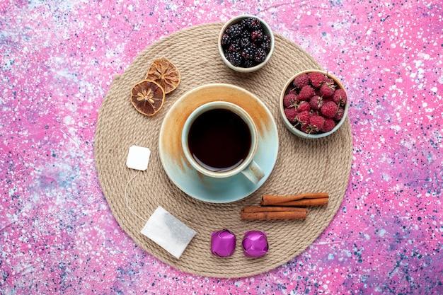Widok z góry świeże jagody maliny i jeżyny z herbatą i cynamonem na różowym biurku.