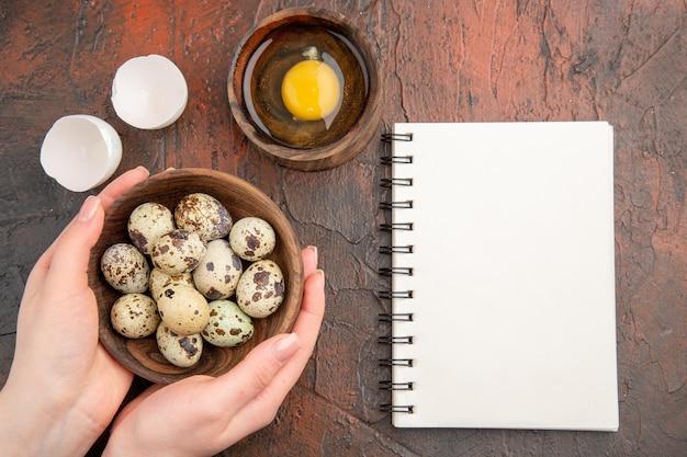 Widok z góry świeże jajka przepiórcze z surowym jajkiem wewnątrz talerza na ciemnym stole