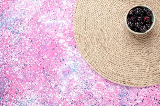 Widok z góry świeże jeżyny w białym garnku na różowym biurku.