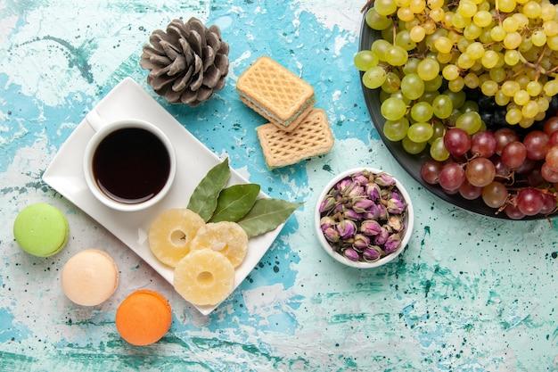 Widok z góry świeże kolorowe winogrona z filiżanką herbaty makaroniki i gofry na jasnoniebieskiej powierzchni owoce jagoda świeży łagodny sok wino