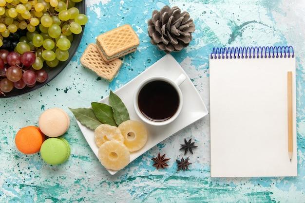 Widok z góry świeże kolorowe winogrona z filiżanką herbaty makaroniki i gofry na jasnoniebieskim tle owoce ciastko cukier słodkie ciasto upiec ciasto