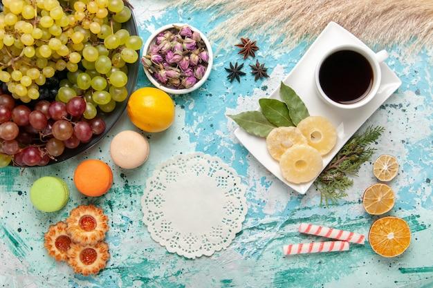 Widok z góry świeże kolorowe winogrona z filiżanką herbaty na jasnoniebieskiej powierzchni owoce ciasteczka cukier słodkie ciasto ciasto do pieczenia