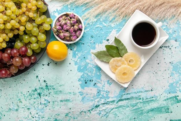 Widok z góry świeże kolorowe winogrona z filiżanką herbaty na jasnoniebieskim tle owoce cookie cukier słodkie ciasto ciasto piecowe