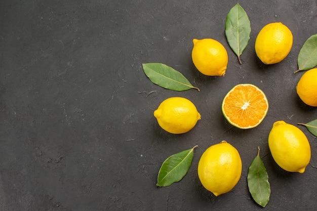 Widok z góry świeże kwaśne cytryny wyłożone ciemną podłogą cytrusowo-żółtymi owocami