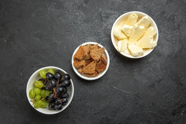 Widok z góry świeże, łagodne winogrona z chlebem i serem na ciemnej powierzchni posiłek spożywczy mleko owoce
