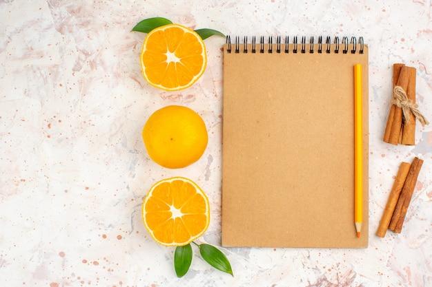 Widok z góry świeże mandarynki cięte mandarynki laski cynamonu ołówek na notebooku na jasnej, odizolowanej powierzchni z wolną przestrzenią