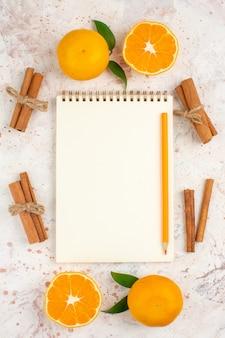 Widok z góry świeże mandarynki notatnik ołówek laski cynamonu na jasnej odizolowanej powierzchni