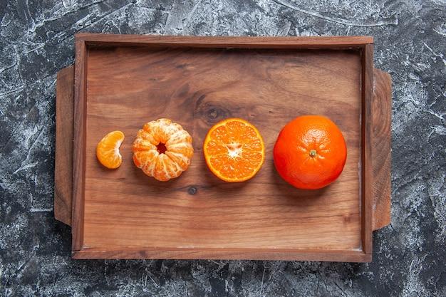 Widok z góry świeże mandarynki obrane mandarynki na drewnianej tacy na szarym stole