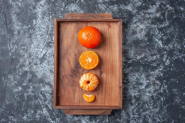 Widok z góry świeże mandarynki obrane mandarynki na drewnianej tacy na szarym tle