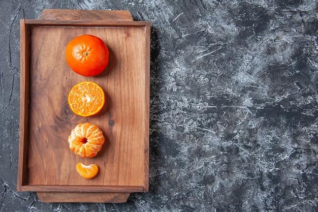Widok z góry świeże mandarynki obrane mandarynki na drewnianej tacy na wolnym miejscu na stole