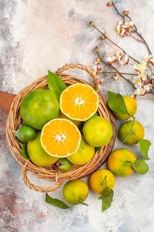 Widok z góry świeże mandarynki w wiklinowym koszu na desce do krojenia na nagim tle