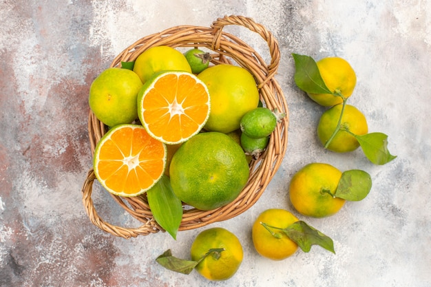 Widok z góry świeże mandarynki w wiklinowym koszu otoczony mandarynkami na nagim tle