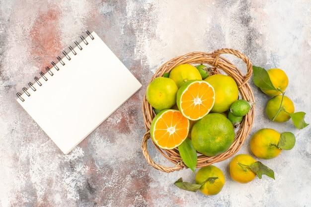 Widok z góry świeże mandarynki w wiklinowym koszu otoczony mandarynkami notatnik na nagim tle