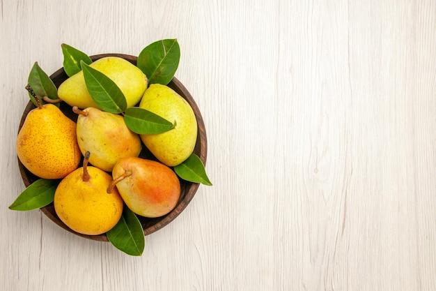 Widok z góry świeże miękkie gruszki słodkie owoce wewnątrz talerza na białym biurku owoce żółte świeże słodkie dojrzałe