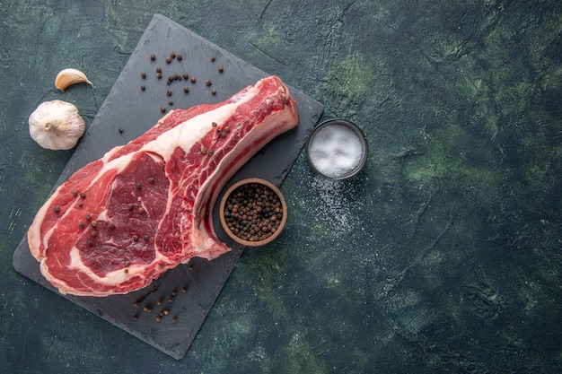 Widok z góry świeże mięso kawałek surowego mięsa z pieprzem na ciemnym tle mączka z kurczaka zdjęcie kolor jedzenie zwierzę rzeźnik