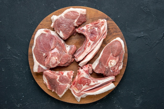 Widok z góry świeże mięso plastry surowe mięso na okrągłym drewnianym biurku na ciemnym jedzeniu świeżość zwierzęca krowa posiłek jedzenie kuchnia