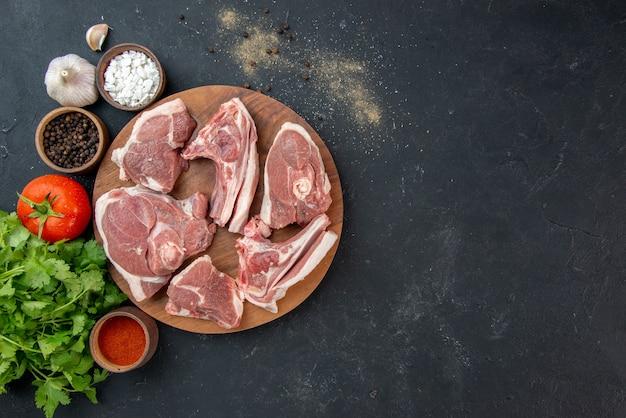 Widok z góry świeże mięso plastry surowe mięso z przyprawami i zieleniną na ciemnej kuchni sałatka posiłek świeżość jedzenie krowa jedzenie zwierzę