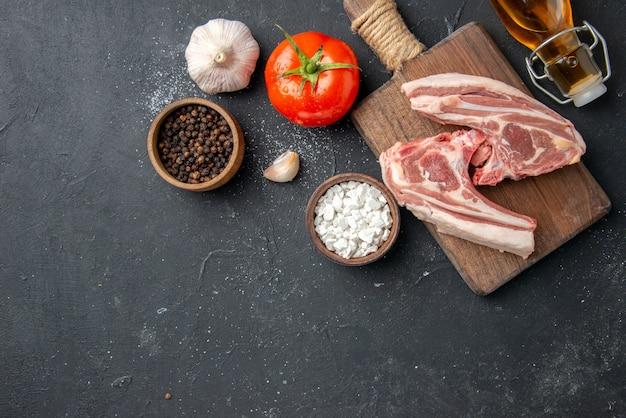 Widok z góry świeże mięso żeberka surowe mięso z olejem i czosnkiem na ciemnym grillu danie dla zwierząt pieprz jedzenie sałatka z krów