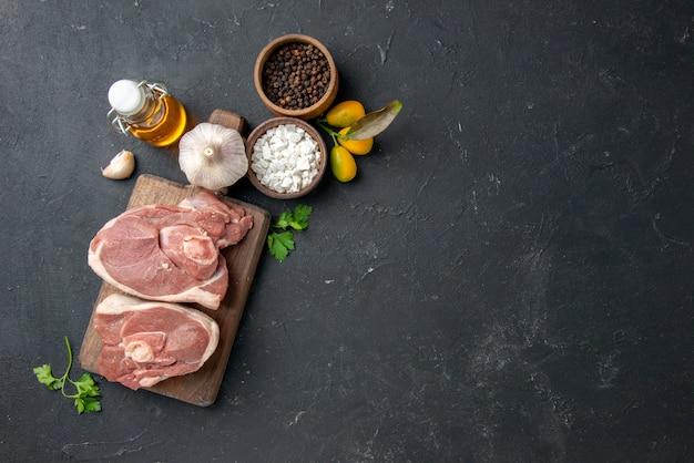 Widok z góry świeże mięso żeberka surowe mięso z przyprawami na ciemnym grillu danie dla zwierząt pieprz jedzenie sałatka posiłek jedzenie gotowanie