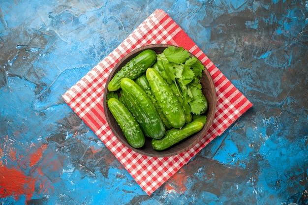Widok z góry świeże ogórki wewnątrz talerza na niebieskim tle sałatka zdrowie zdjęcie dojrzały posiłek jedzenie dieta kolor