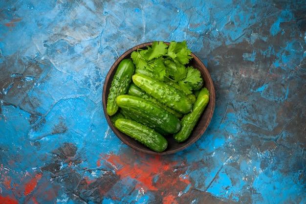 Widok z góry świeże ogórki wewnątrz talerza na niebieskim tle zdjęcie kolor dojrzała sałatka posiłek spożywczy