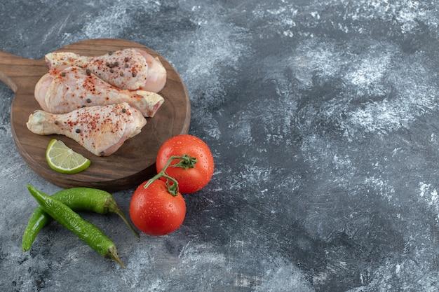 Widok z góry. świeże, organiczne pomidory i papryka z surowymi udkami z kurczaka