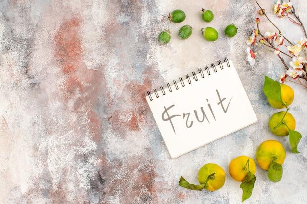 Widok z góry świeże owoce mandarynki feykhoa napisane na notebooku na nagim tle