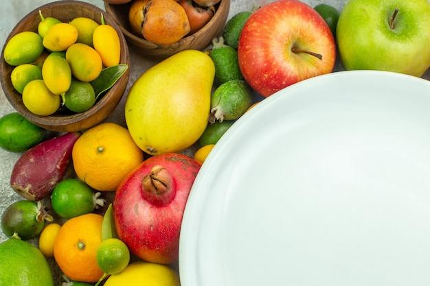 Widok z góry świeże owoce różne łagodne owoce na białym biurku dojrzałe jagody dieta smaczny kolor drzewo zdrowie