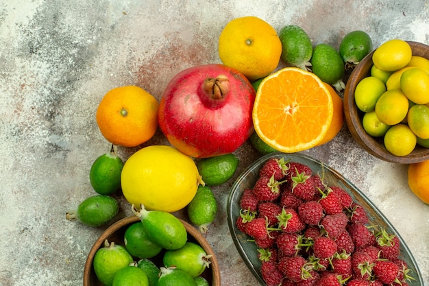 Widok z góry świeże owoce różne łagodne owoce na białym tle zdrowie drzewo kolor smaczne zdjęcie dojrzałe jagody cytrusowe