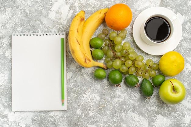 Widok z góry świeże owoce skład jabłka winogrona i banany z kawą na białym tle świeże łagodne owoce dojrzałe kolor vitamine